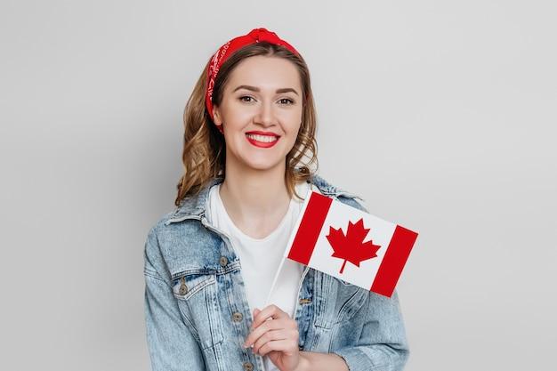 Młoda studentka uśmiechnięta i trzymająca małą flagę kanady na białym tle nad szarą ścianą, dzień kanady, wakacje, rocznica konfederacji, miejsce na kopię
