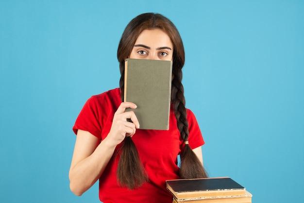 Młoda studentka w czerwonej koszulce chowa się za książką na niebieskiej ścianie.
