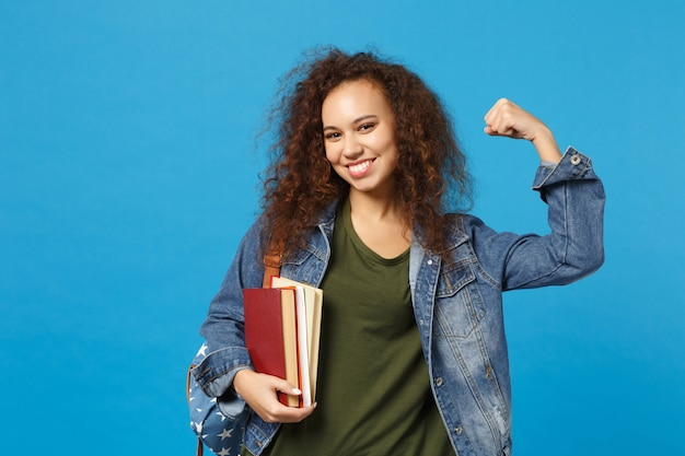 Młoda studentka w dżinsowych ubraniach i plecaku trzyma książki izolowane na niebieskiej ścianie