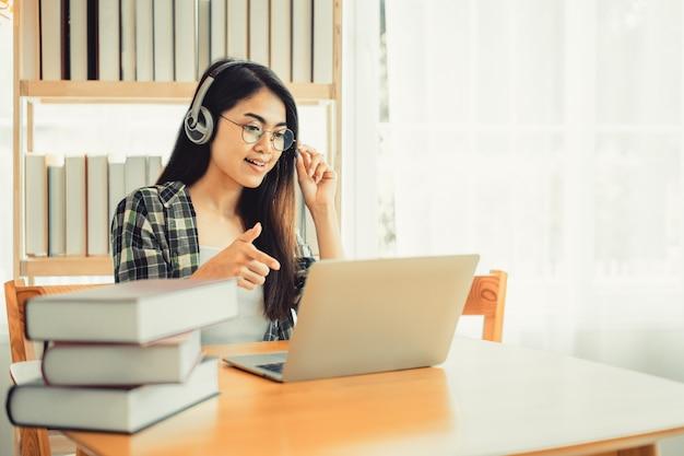 Młoda studentka w koszuli w kratę siedzi przy stole za pomocą laptopa podczas nauki.