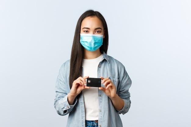 Młoda studentka w masce medycznej pokazując kartę kredytową, zamówienie online, otwarte konto bankowe