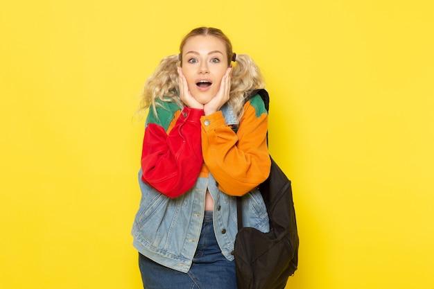 Młoda studentka w nowoczesnych ubraniach po prostu pozuje z zaskoczeniem na żółto