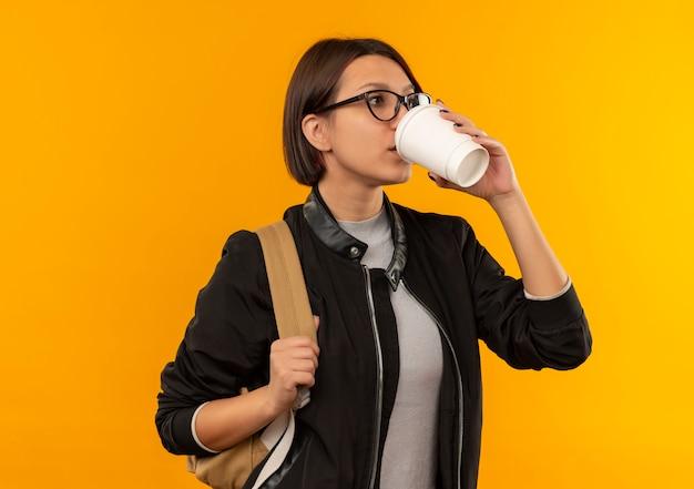 Młoda studentka w okularach i worek z powrotem picia kawy z plastikowej filiżanki kawy patrząc z boku na białym tle na pomarańczowym tle