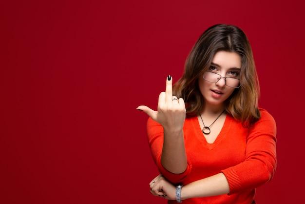 Młoda studentka w okularach pokazuje nieprzyzwoite gesty środkowy palec