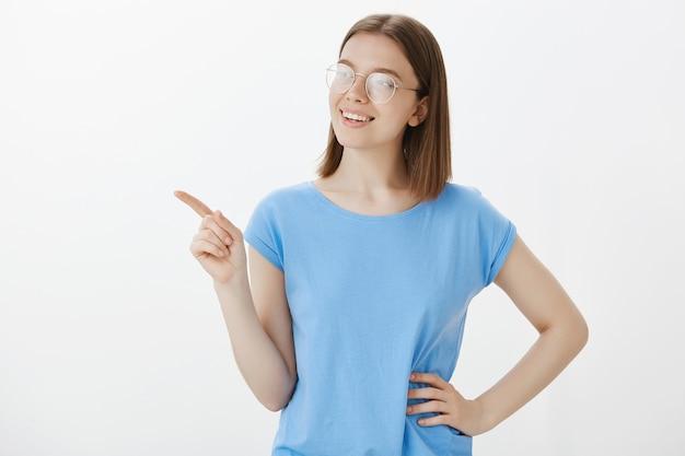 Młoda studentka w okularach, uśmiechając się i wskazując palcem w lewym górnym rogu