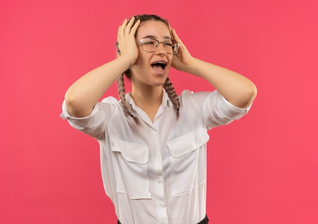 Młoda studentka w okularach z warkoczykami w białej koszuli patrząc na bok, trzymając głowę rękami krzyczącymi w panice, stojąc nad różową ścianą