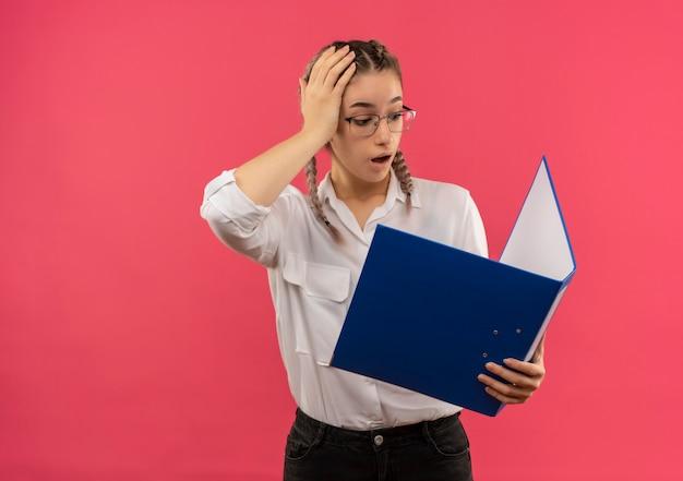Młoda studentka w okularach z warkoczykami w białej koszuli patrząc na otwarty folder w dłoniach wyglądająca na zdezorientowaną i bardzo niespokojną stojącą nad różową ścianą
