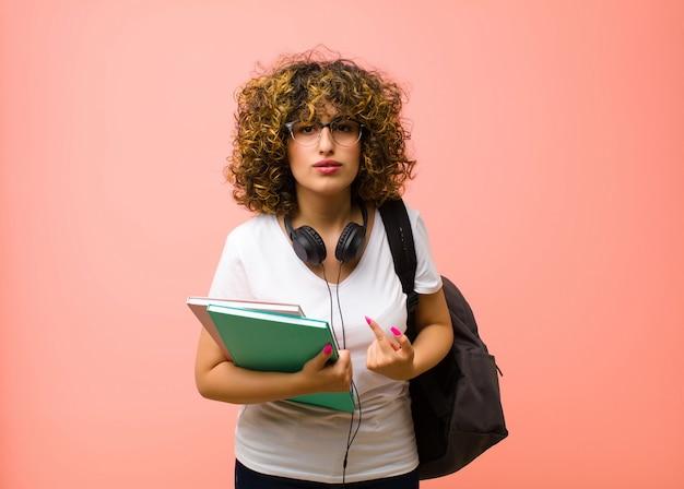Młoda studentka wskazująca na siebie ze zdezorientowanym i zagadkowym spojrzeniem, zszokowana i zaskoczona wyborem na różowej ścianie