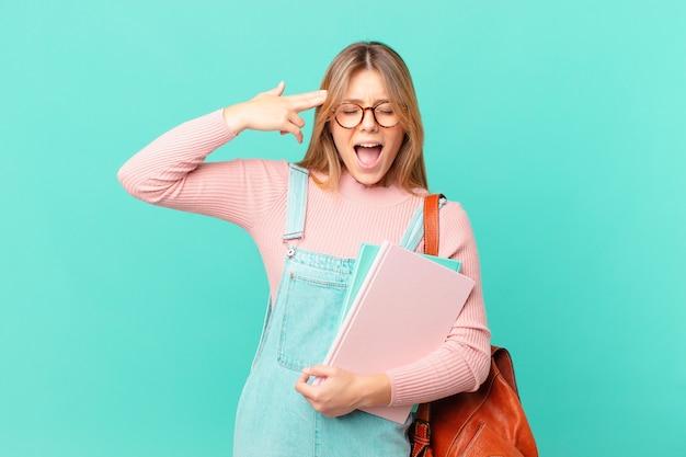 Młoda studentka wyglądająca na niezadowoloną i zestresowaną, gest samobójczy robiący znak pistoletu