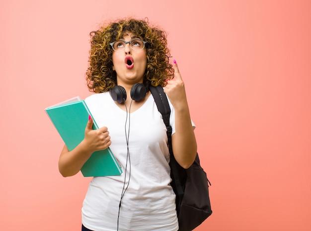 Młoda studentka wyglądająca na zszokowaną, zdumioną i otwartą ustami, wskazująca w górę obiema rękami, aby skopiować miejsce na różowej ścianie