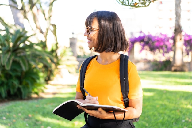 Młoda studentka wygrywa park trzymając zeszyt
