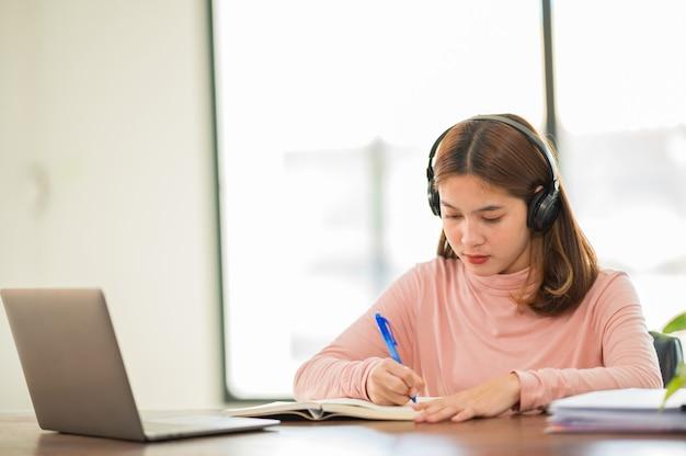 Młoda studentka z azji w słuchawkach, aby uczyć się online w domu, w czasie epidemii wirusa i nie uczęszczała na uniwersytet.