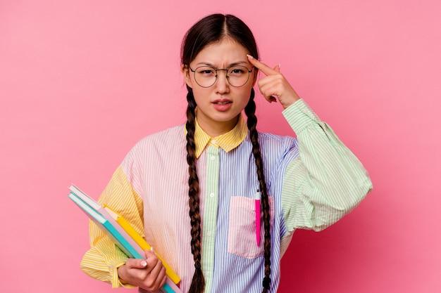 Młoda studentka z chin, trzymająca książki, ubrana w modną wielokolorową koszulę i warkocz, odizolowane na różowym tle pokazując gest rozczarowania palcem wskazującym.