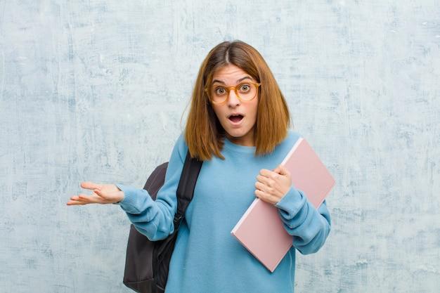 Młoda studentka z otwartymi ustami i zdziwiona, zszokowana i zdziwiona niesamowitą, zaskakującą ścianą grunge