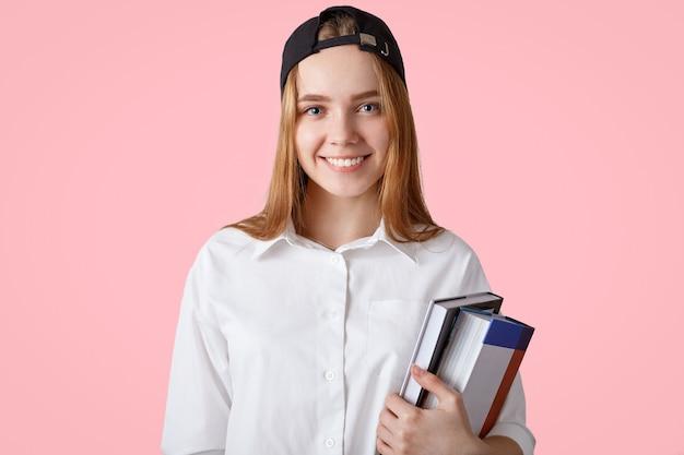 Młoda studentka z pozytywnym uśmiechem, nosi stylową czapkę i białą koszulę, trzyma stos książek, jest gotowa na wykłady, idzie do domu, na białym tle nad różową ścianą koncepcja nauki