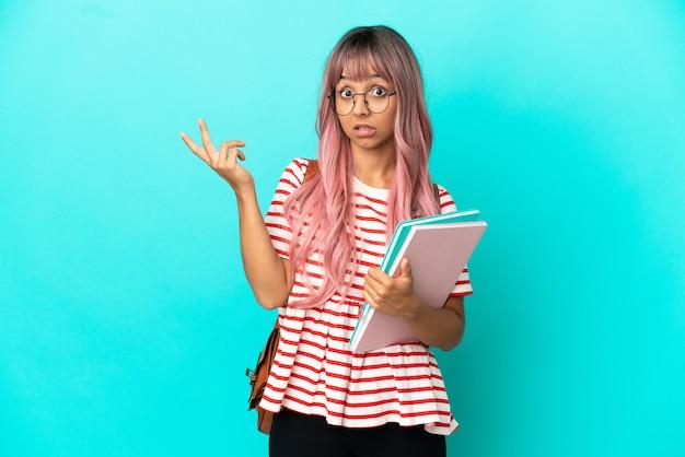 Młoda studentka z różowymi włosami na białym tle na niebieskim tle, wyciągając ręce do boku, zapraszając do przyjścia