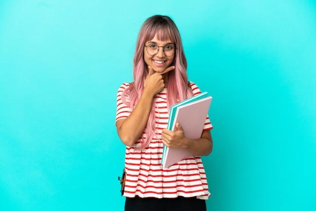Młoda studentka z różowymi włosami na niebieskim tle szczęśliwa i uśmiechnięta
