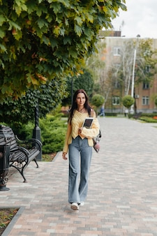 Młoda studentka z tabletem w dłoniach spaceruje po parku.