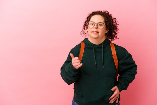 Młoda studentka z zespołem downa na białym tle na różowym tle wskazuje z dala od kciuka, śmiejąc się i beztrosko.