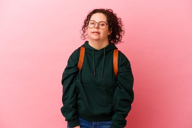Młoda studentka z zespołem downa na różowej ścianie wygląda na bok uśmiechnięta, wesoła i przyjemna