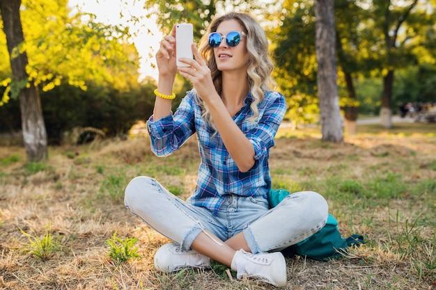 Młoda stylowa atrakcyjna uśmiechnięta blond kobieta siedzi w parku, styl casual lato