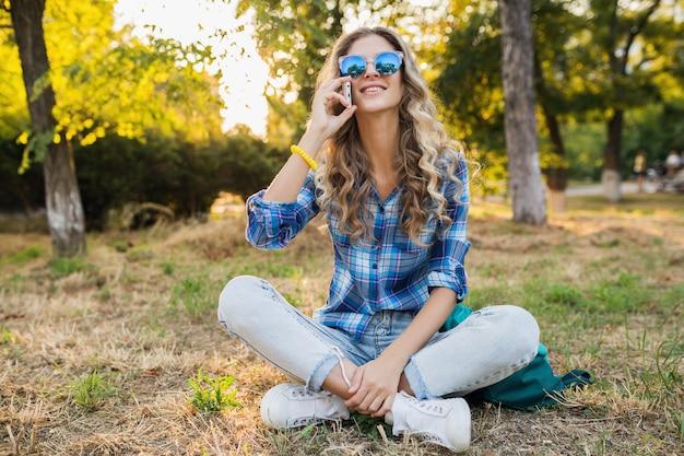 Młoda stylowa całkiem uśmiechnięta szczęśliwa blond kobieta w parku w słoneczny letni dzień