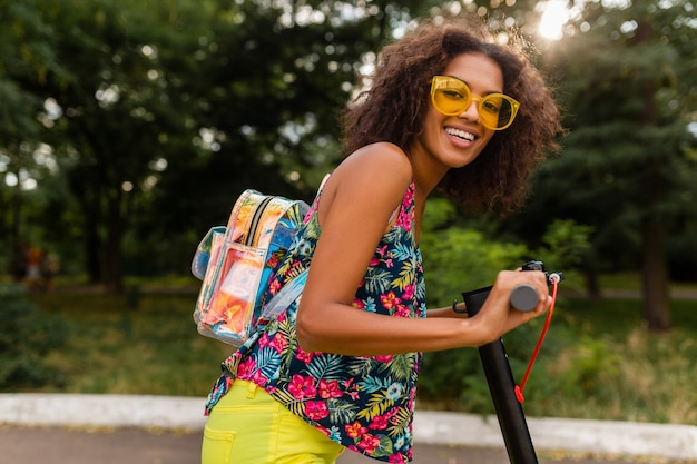 Młoda stylowa czarna kobieta bawi się w parku, jeżdżąc na hulajnodze elektrycznej w letnim stylu mody, kolorowy strój hipster, ubrany w plecak i żółte okulary przeciwsłoneczne