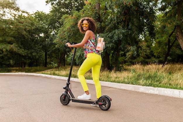 Młoda stylowa czarna kobieta bawi się w parku, jeżdżąc na hulajnodze elektrycznej w letnim stylu mody, kolorowy strój hipster, ubrany w plecak i żółte spodnie i okulary przeciwsłoneczne