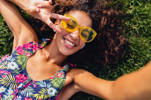 Młoda stylowa czarna kobieta słuchanie muzyki na bezprzewodowych słuchawkach, zabawa w parku, letni styl mody, kolorowy strój hipster, leżąc na trawie, widok z góry