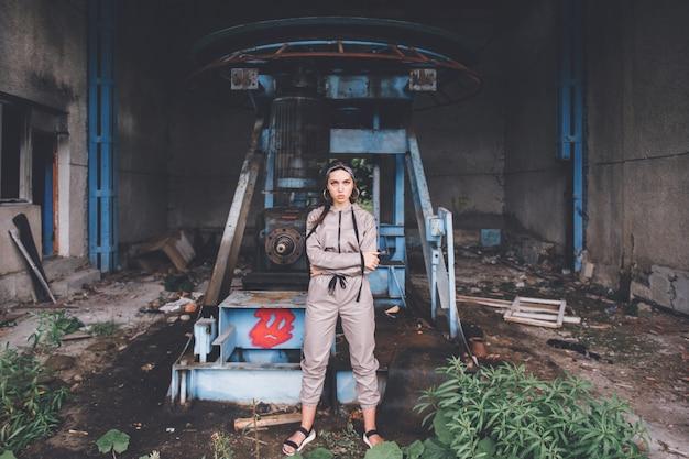 Młoda stylowa dziewczyna pozuje przy zaniechany fabryczny plenerowym