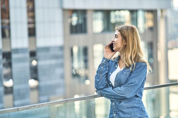 Młoda stylowa dziewczyna ubrana w dżinsową odzież spędzająca wolny czas na świeżym powietrzu
