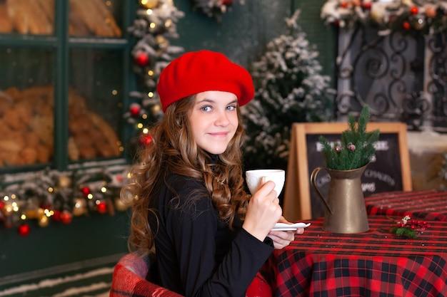 Młoda stylowa dziewczyna w berecie relaks na tarasie kawiarni