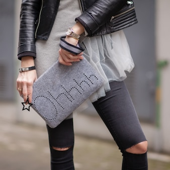 Młoda stylowa dziewczyna w czarnej skórzanej kurtce z torebką w ona ręki