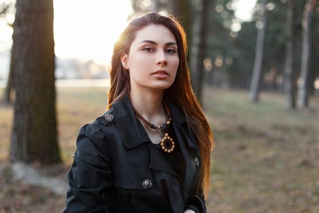 Młoda stylowa dziewczyna w czarnym płaszczu w parku o zachodzie słońca