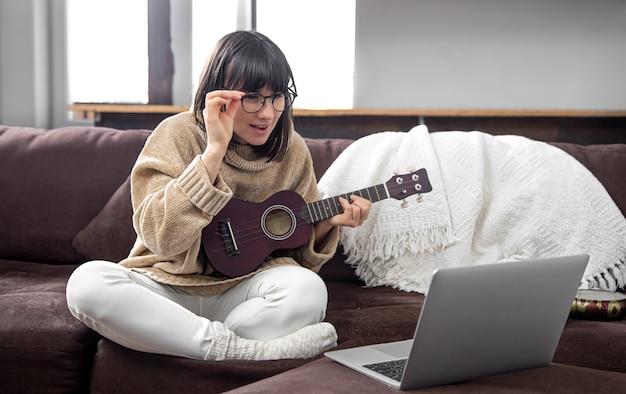 Młoda stylowa dziewczyna w okularach uczy się grać na ukulele. edukacja online, edukacja domowa.
