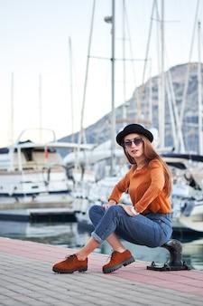 Młoda stylowa dziewczyna w porcie morskim
