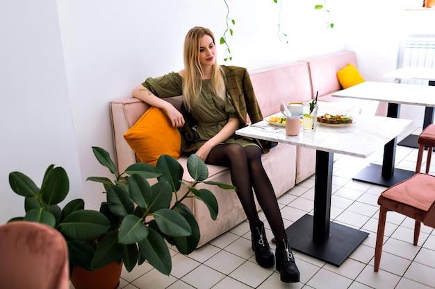 Młoda stylowa elegancka kobieta cieszy się jej smaczne śniadanie w stylowej kawiarni hipster, poranek, elegancki strój.