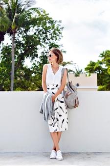 Młoda stylowa hipster kobieta nosi okulary przeciwsłoneczne plecak, spódnicę midi vintage i trampki, spaceruje po ulicy w ładny słoneczny letni dzień, jasne, świeże kolory.