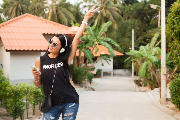 Młoda stylowa hipster kobieta w czarnej koszulce, dżinsy, słuchanie muzyki na słuchawkach, zabawa, spacery po ulicy, letnie wakacje, ciesząc się