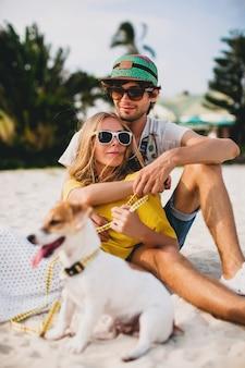 Młoda stylowa hipster para zakochanych spacery grając psa szczeniaka jack russell, tropikalna plaża, fajny strój, romantyczny nastrój, zabawa, słonecznie, mężczyzna kobieta razem, poziome, wakacje, dom willa