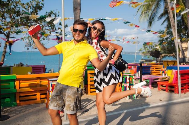 Młoda stylowa hipster piękna para na wakacjach w tajlandii, zalotne, modny strój, okulary przeciwsłoneczne, tropikalny romans, uśmiechnięty, szczęśliwy, słuchanie muzyki, imprezowy nastrój, kawiarnia na plaży