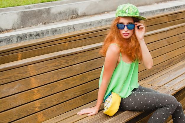 Młoda, stylowa hipster ruda kobieta, siedzi na ławce, zielona czapka, legginsy, torebka, okulary przeciwsłoneczne, zabawa, modna odzież, modny strój, miejski styl nastolatka