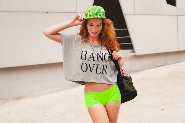 Młoda stylowa hipster ruda kobieta, spacerująca po ulicy, zielona czapka, szara koszulka oversize, zabawa, modna odzież, modny strój, miejski styl nastolatka, plecak, podróżnik