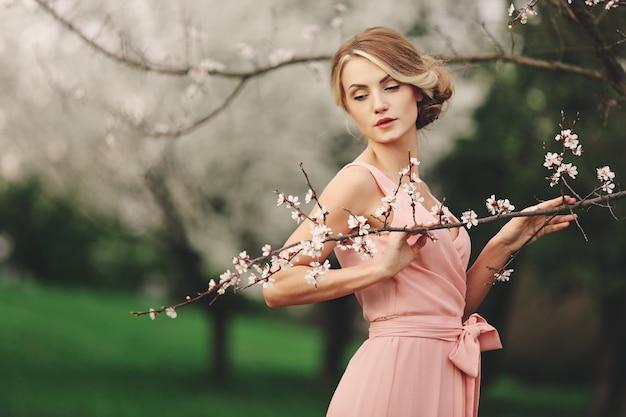 Młoda stylowa kobieta blisko kwitnie kwitnącego drzewa w parku. blondynka z fryzurą w różowej sukience.