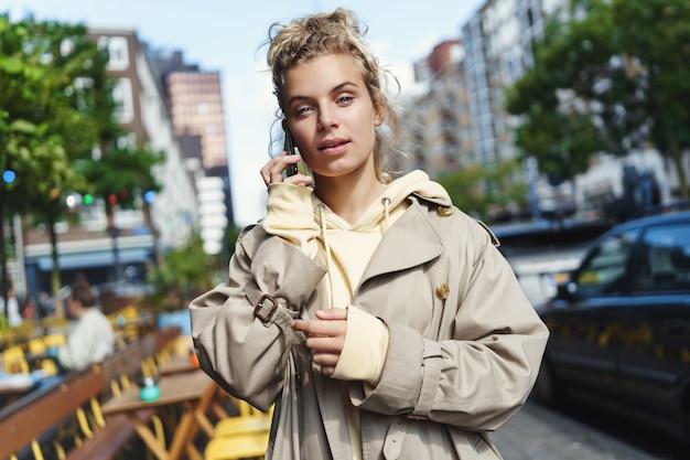 Młoda stylowa kobieta idzie ulicą i rozmawia przez telefon, rano dojeżdża do biura.