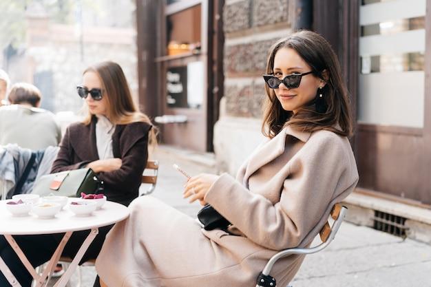 Młoda stylowa kobieta pozuje w nowożytnej ulicznej kawiarni.