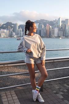 Młoda stylowa kobieta pozuje w porcie wiktorii w hongkongu.