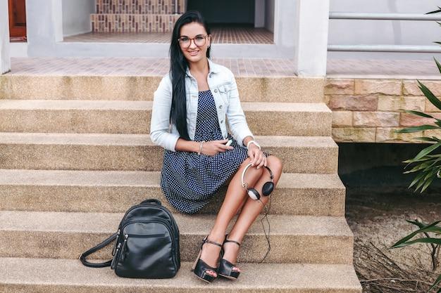 Młoda stylowa kobieta siedzi na schodach, trzymając słuchawki w rękach, plecak, długie nogi, buty na wysokim obcasie, opalona skóra, szczegóły zbliżenie, akcesoria
