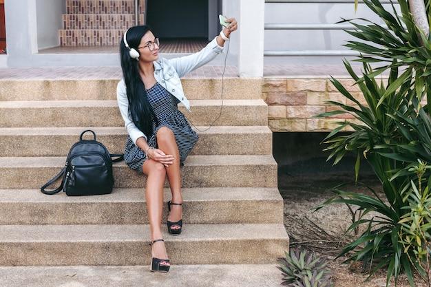 Młoda stylowa kobieta siedzi na schodach ze smartfonem, słuchanie muzyki na słuchawkach, robienie zdjęć