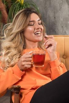 Młoda stylowa kobieta siedzi w fotelu, je czekoladę i trzyma herbatę.